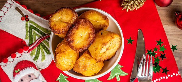 Roast potatoes in a bowl on a Christmas table cloth