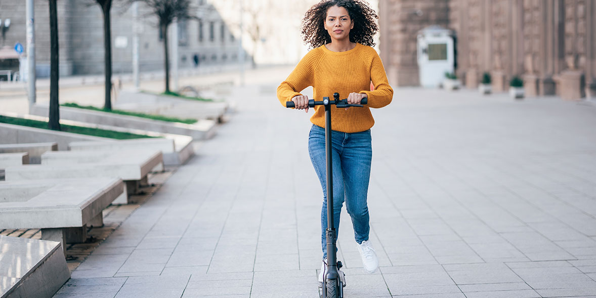 A woman riding an electric scooter