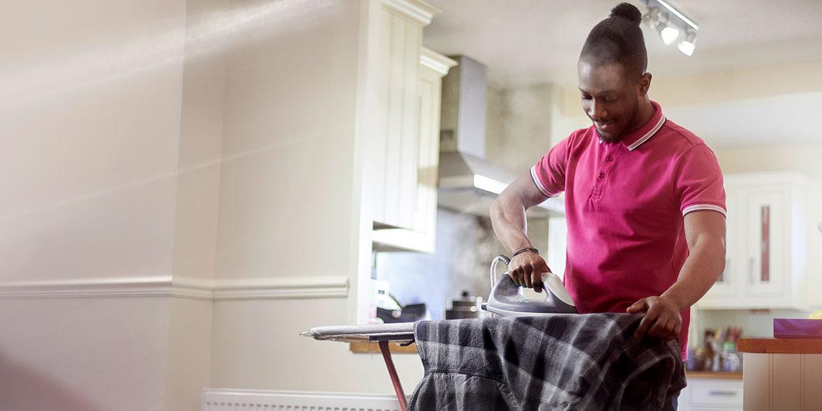 Man ironing chequered shirt