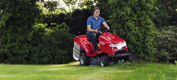 Man using a red lawn tractor