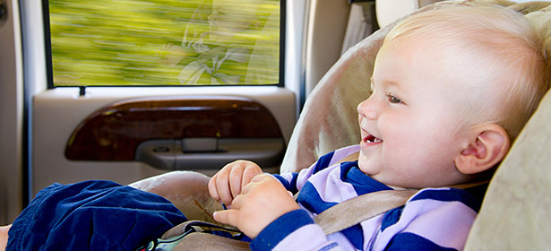 Smiling baby in child car seat