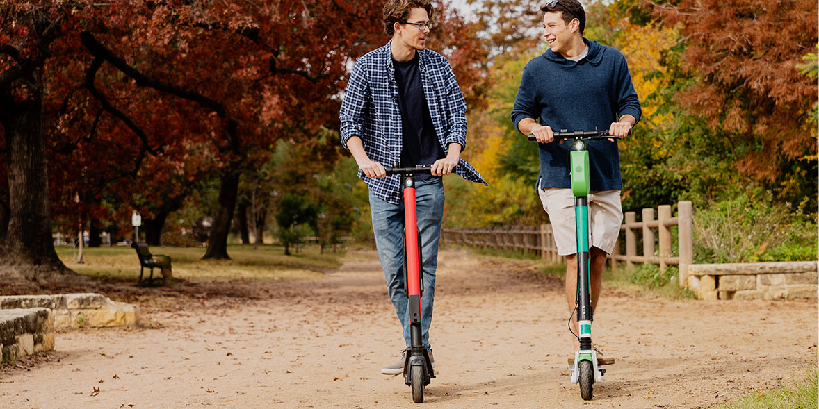 Two friends riding electric scooters in a park