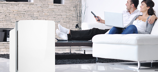 Couple sitting on a sofa with an air purifier in the corner of the room